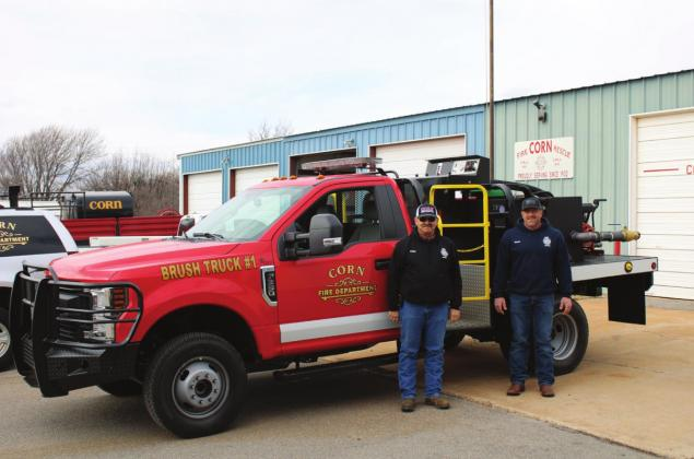Corn firefighters Bart Gossen, left, and Sean Estes show off the department's new brush truck. Bob Henline | The Cordell Beacon
